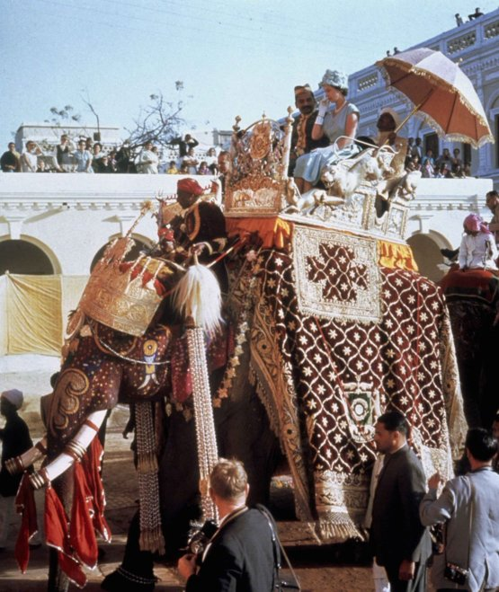 Queen Elizabeth II perches on the back of an elephant during her tour of India, 1961.