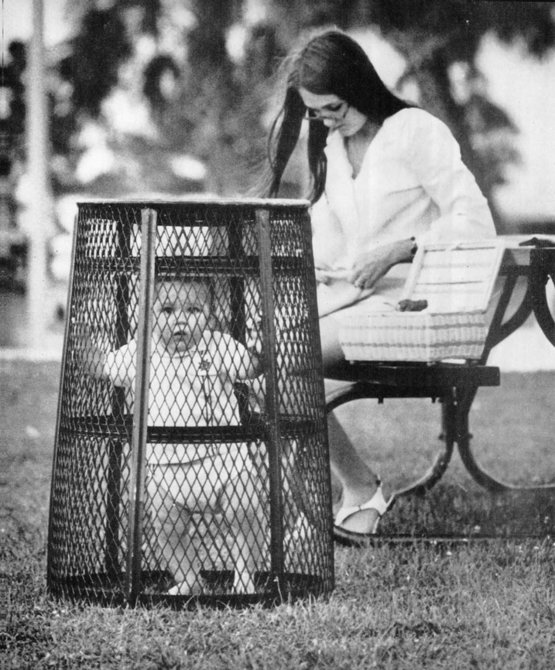 mom uses a trash can to contain her baby while she crochets in the park, 1969.