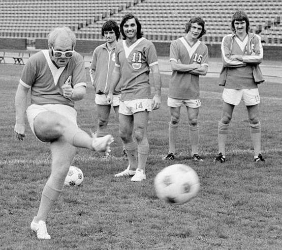 Elton John kicking a football while George Best and some of his teammates are watching