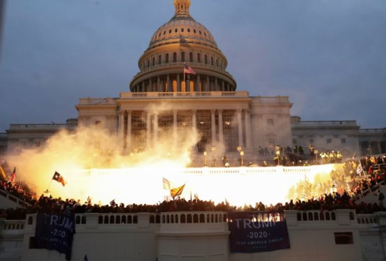 A flash bang lights up the steps of the Capitol Building as Trump supporters refuse to back down