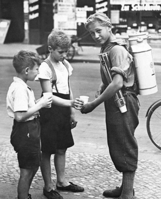 A boy selling lemonade with a portable lemonade dispenser. Berlin, 1931.