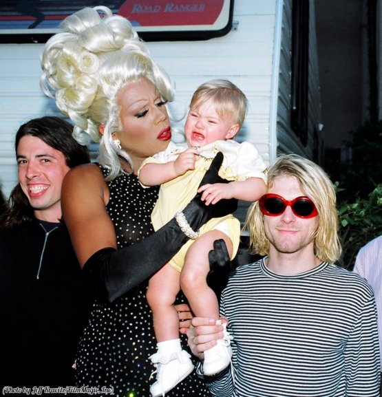 Dave Grohl and Kurt Cobain smirk while RuPaul tries to console a screaming Frances Bean, 1993.