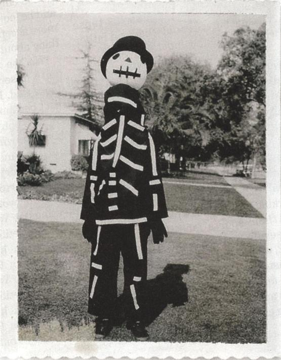 Tim Burton showing off a Halloween costume made by his mother, 1967.